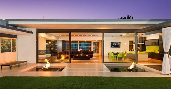 Retractable glass walls open up to the backyard patio from the living room